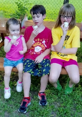kids eating ice cream on a picnic table.