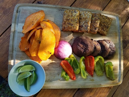 grilled sweet potatoes, portabella mushrooms, red onion, bell peppers, and tempeh on a wooden cutting board with a white bowl of lime wedges.